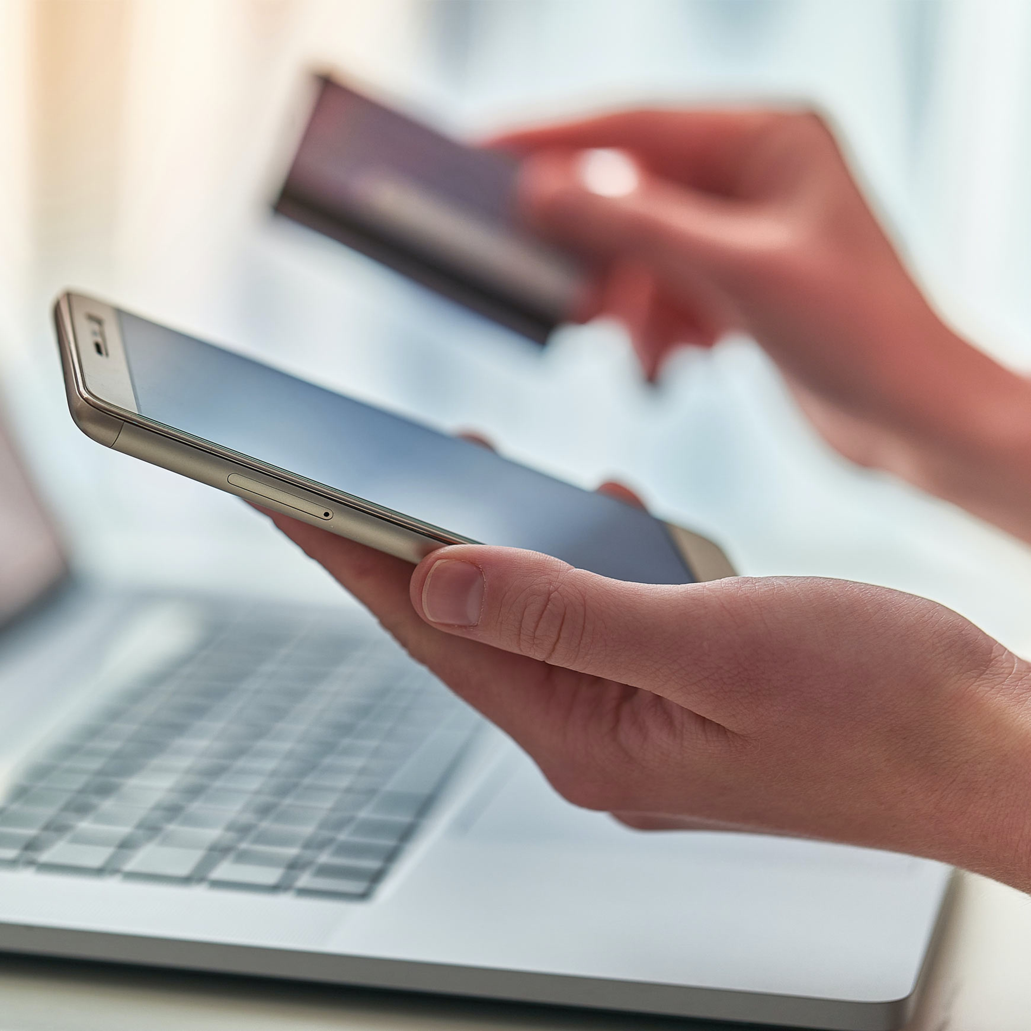 someone using credit card and smartphone and laptop