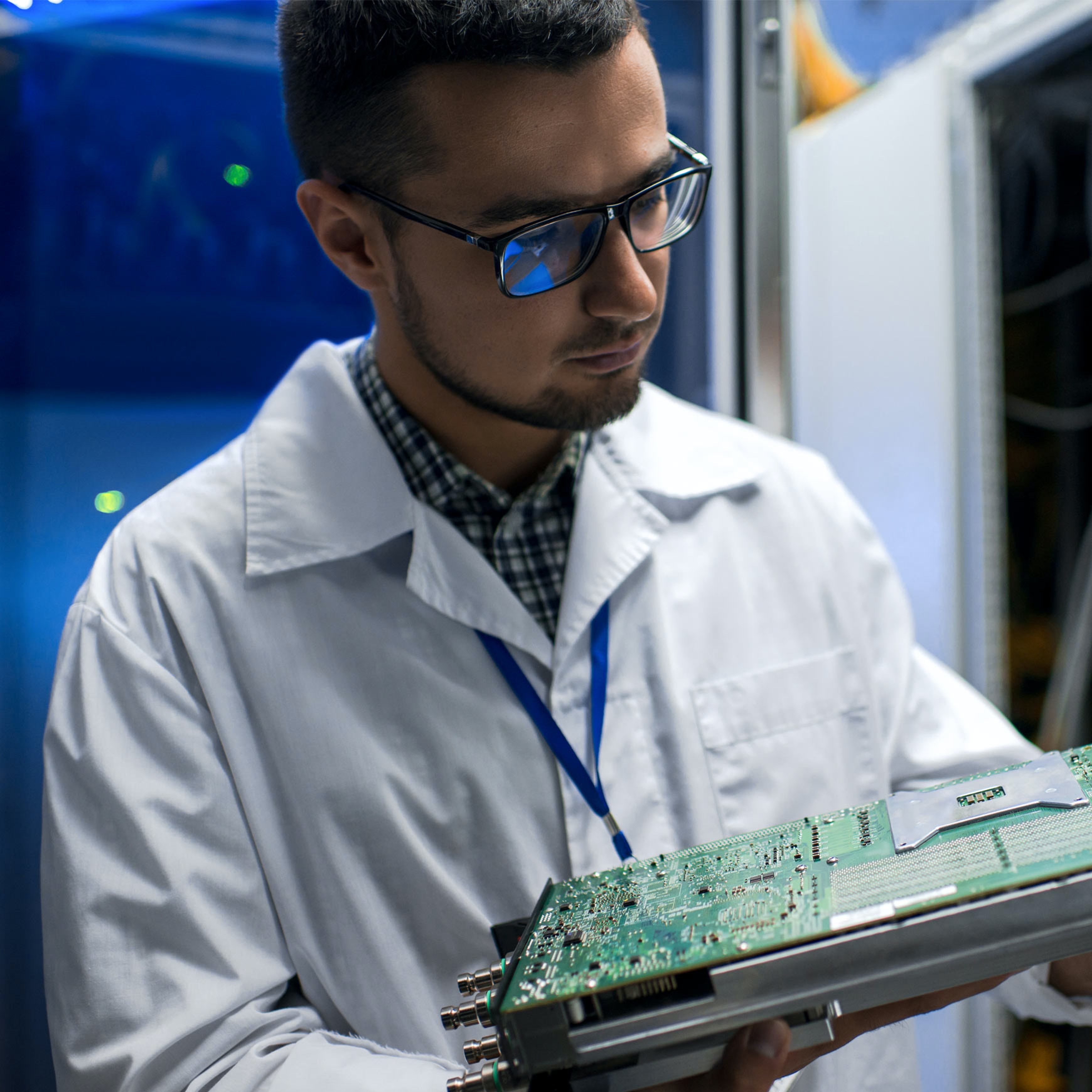 male employee in lab coat looking at motherboard