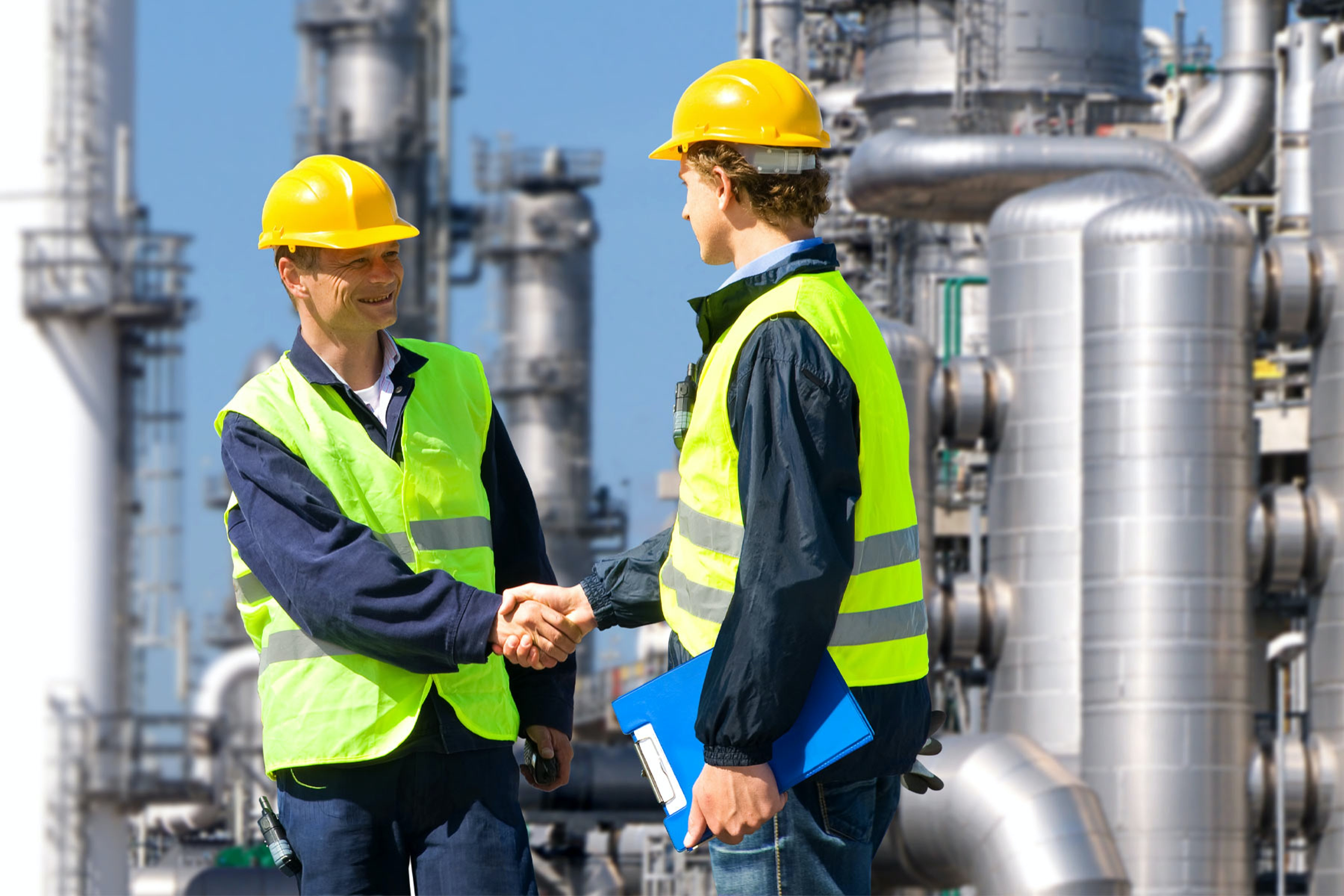 field workers shaking hands in high vis clothing in a chemical plant