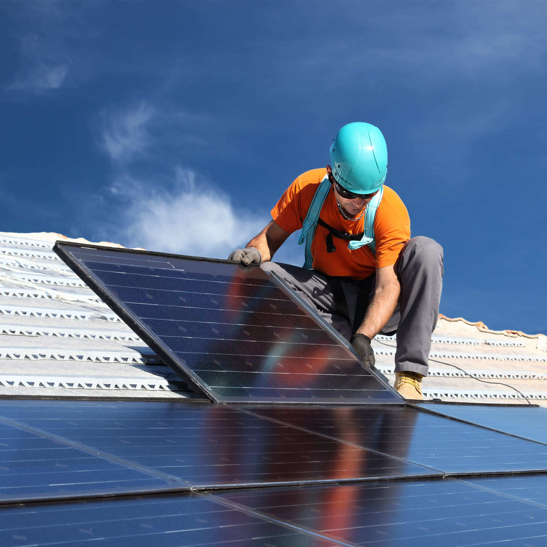 field worker putting a solar panel in place on house.