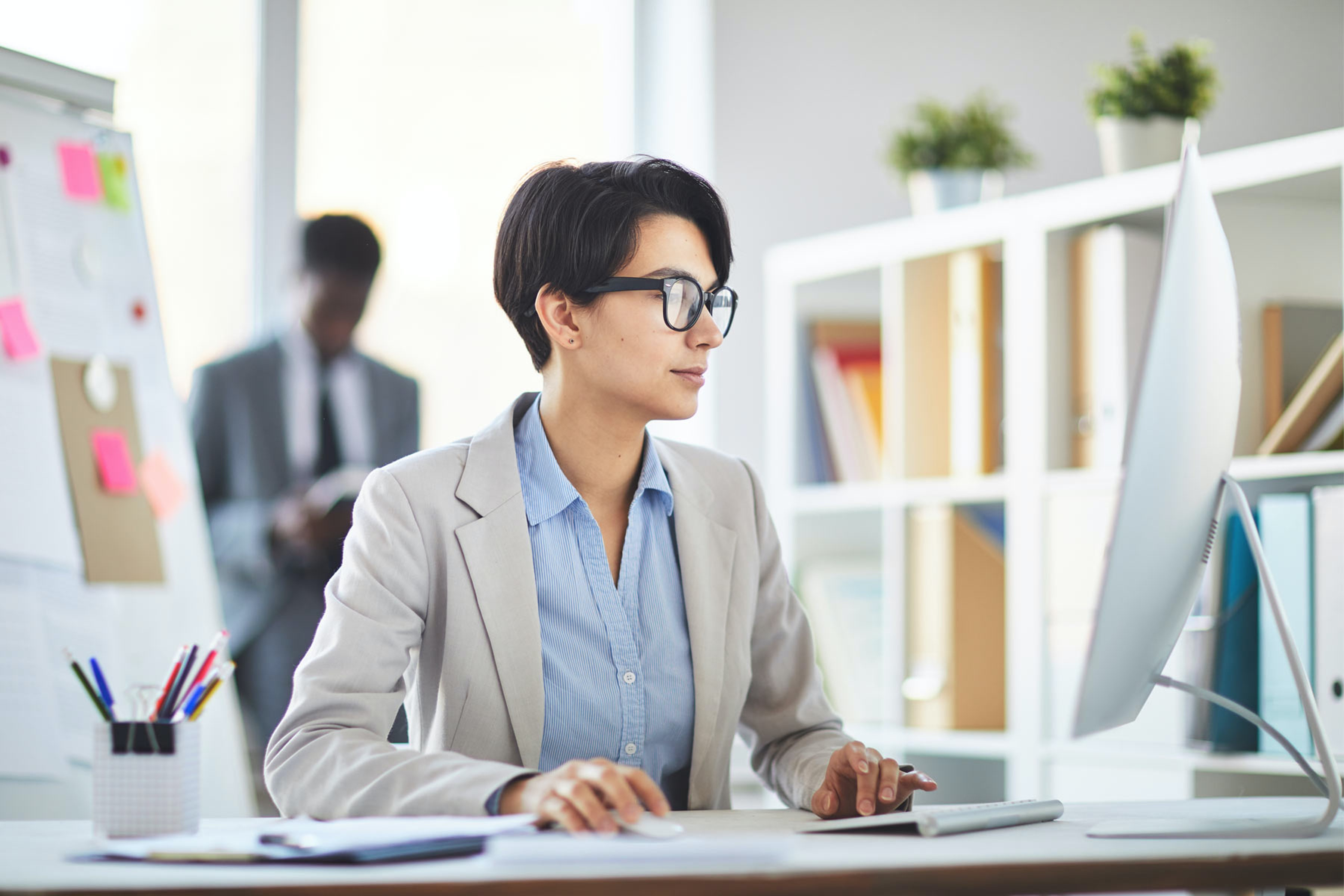 employee using computer at a desk in office environment