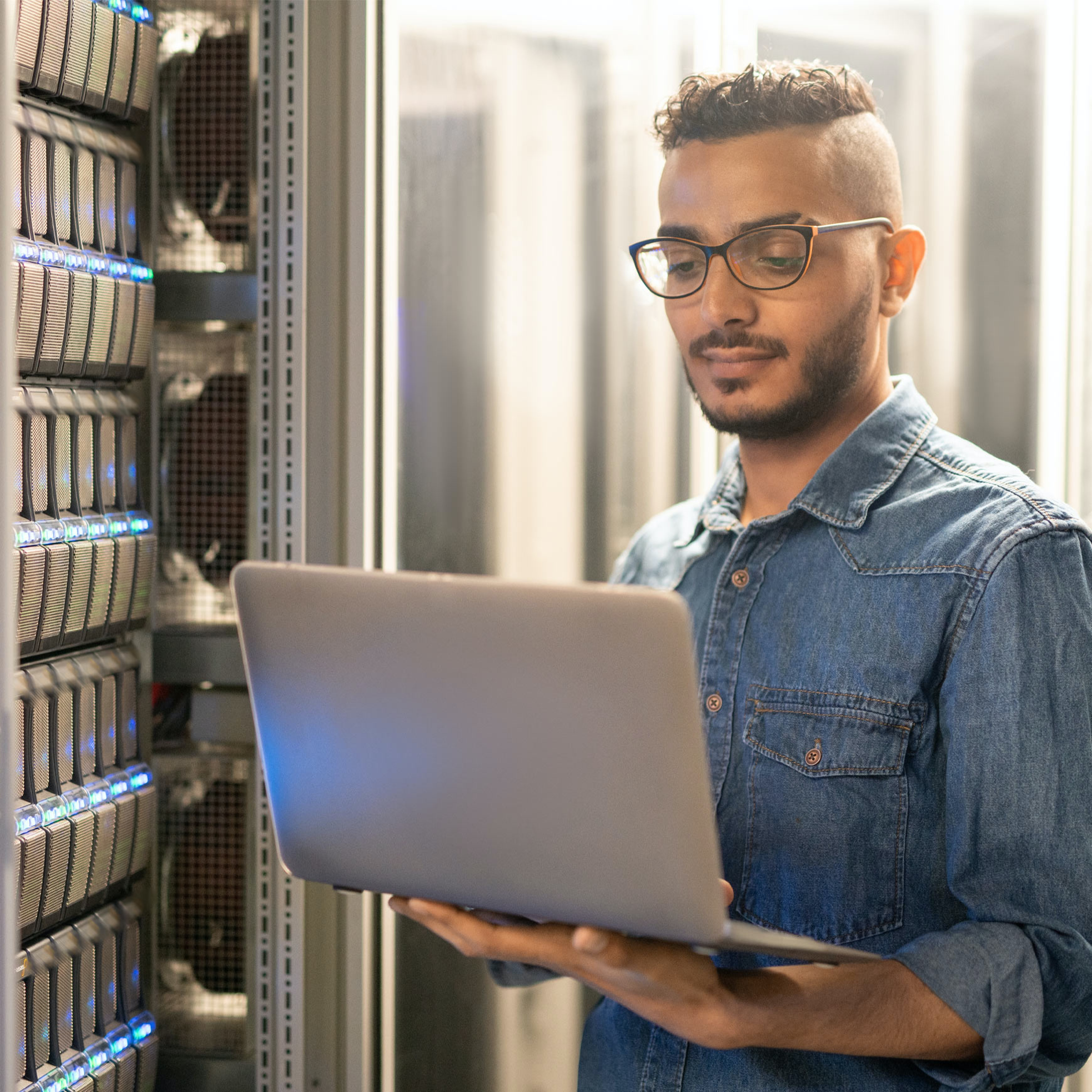male employee uses laptop next to servers