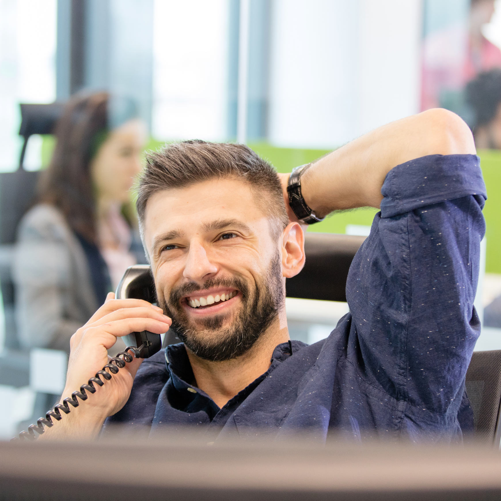 male employee on the phone and smiling in an office