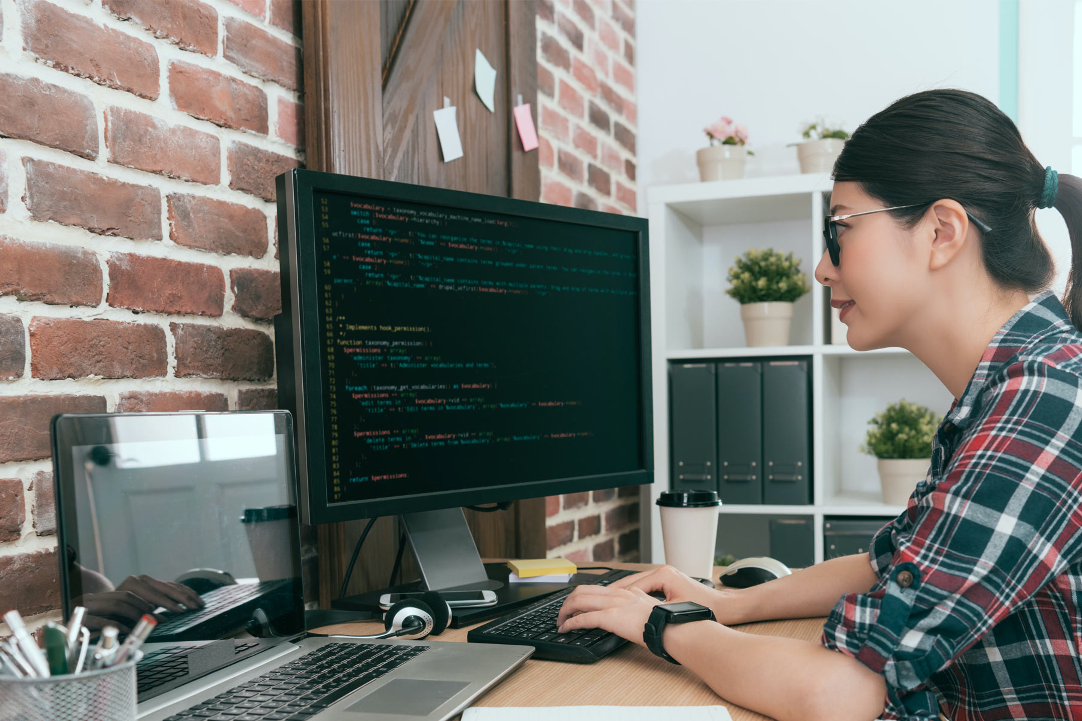 woman at home coding on computer at desk
