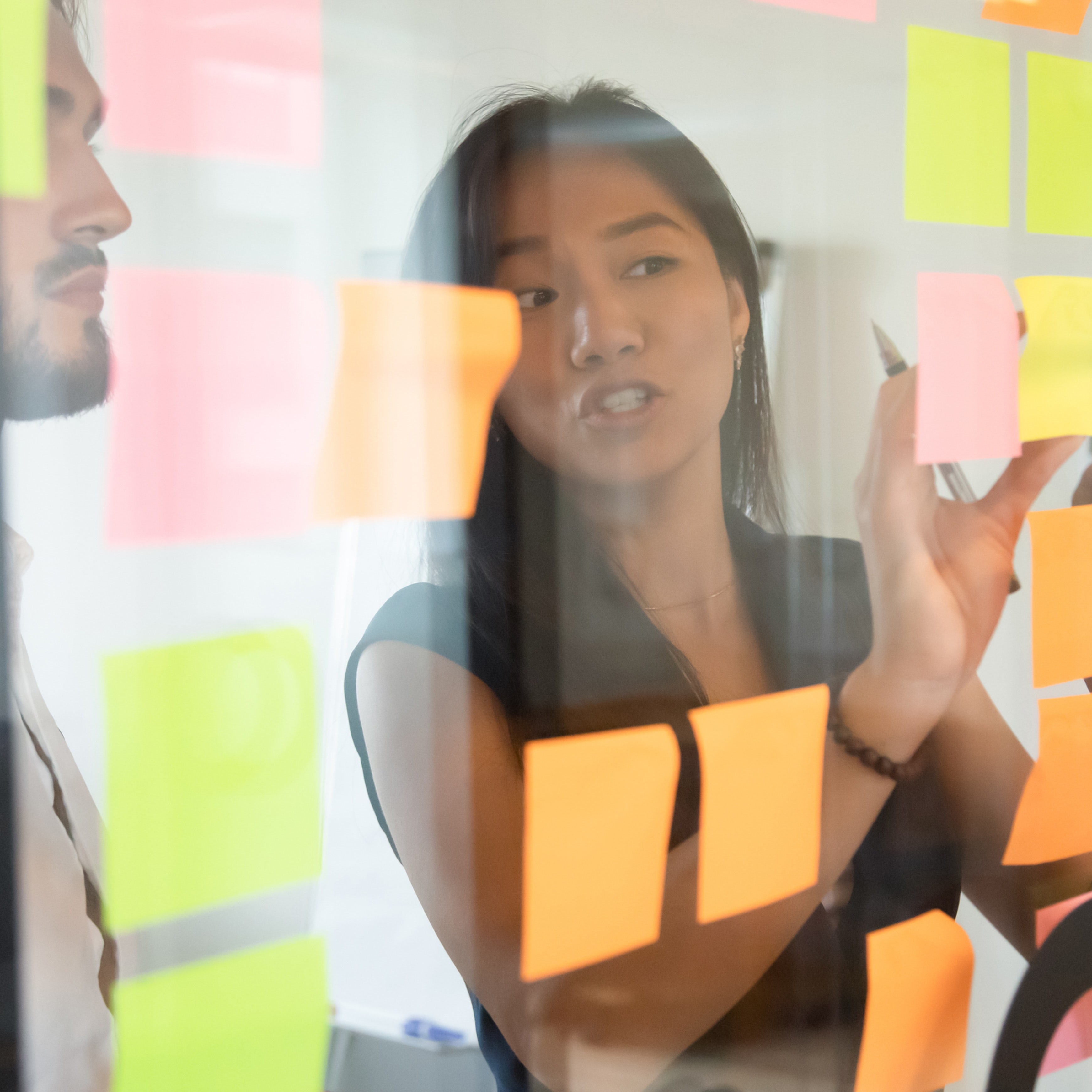 female employee putting post-its on board