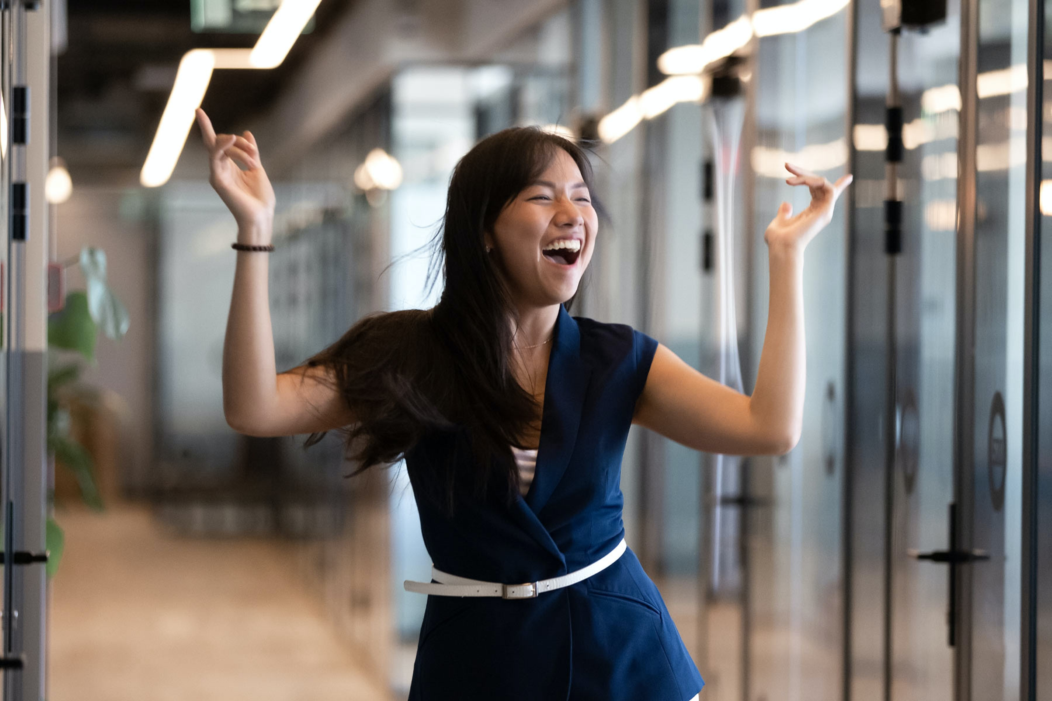 a happy employee smiles and dances down a corridor