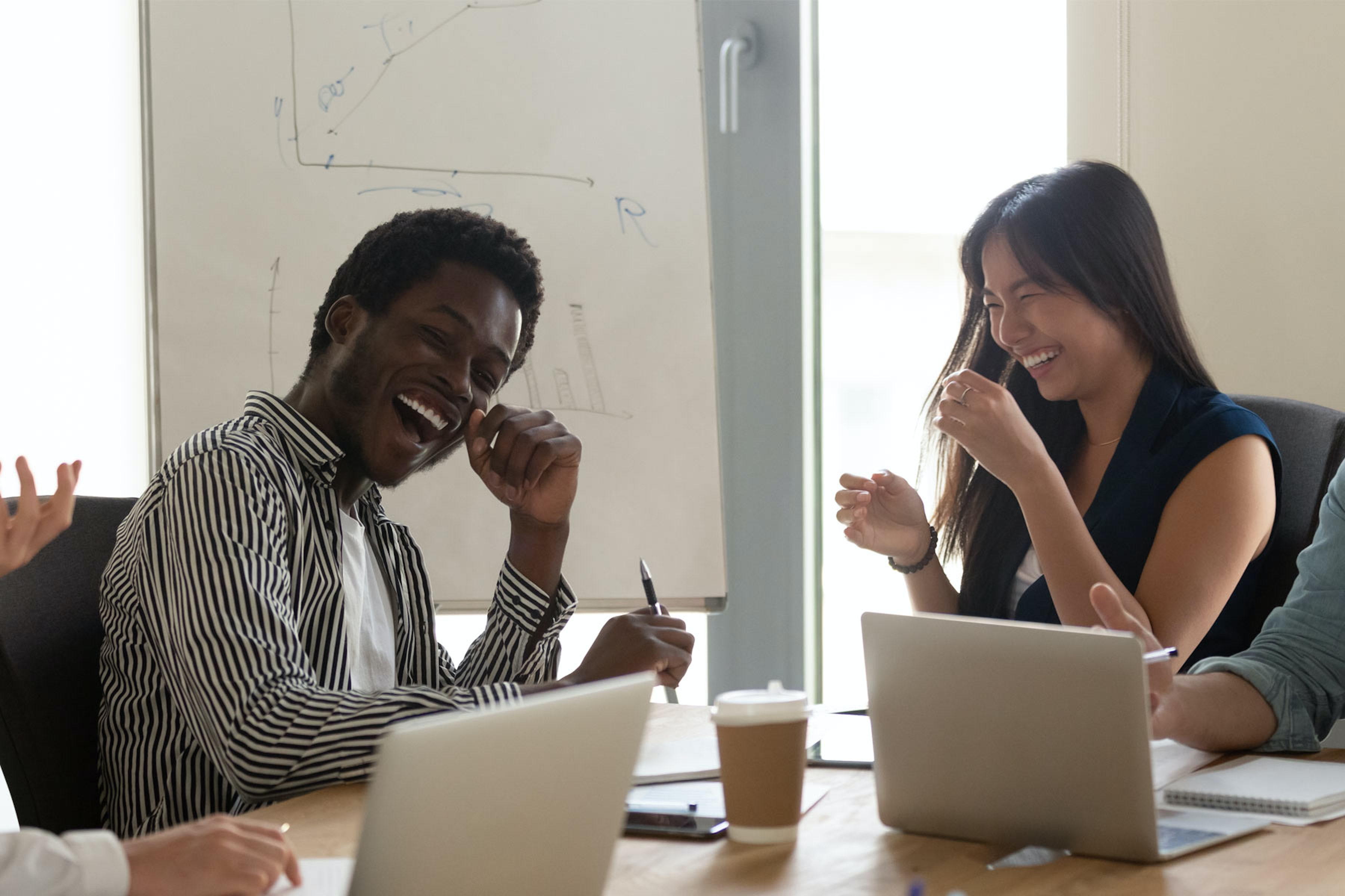 two employees laugh together in a meeting