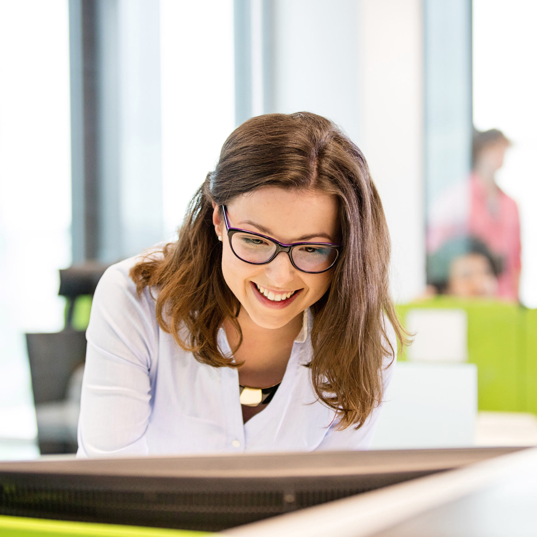 smiling female employee looking at computer in office
