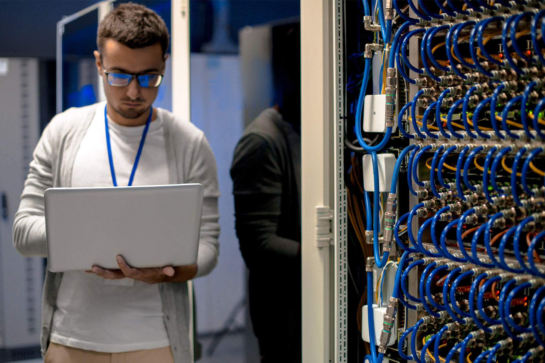 male employee using laptop next to servers