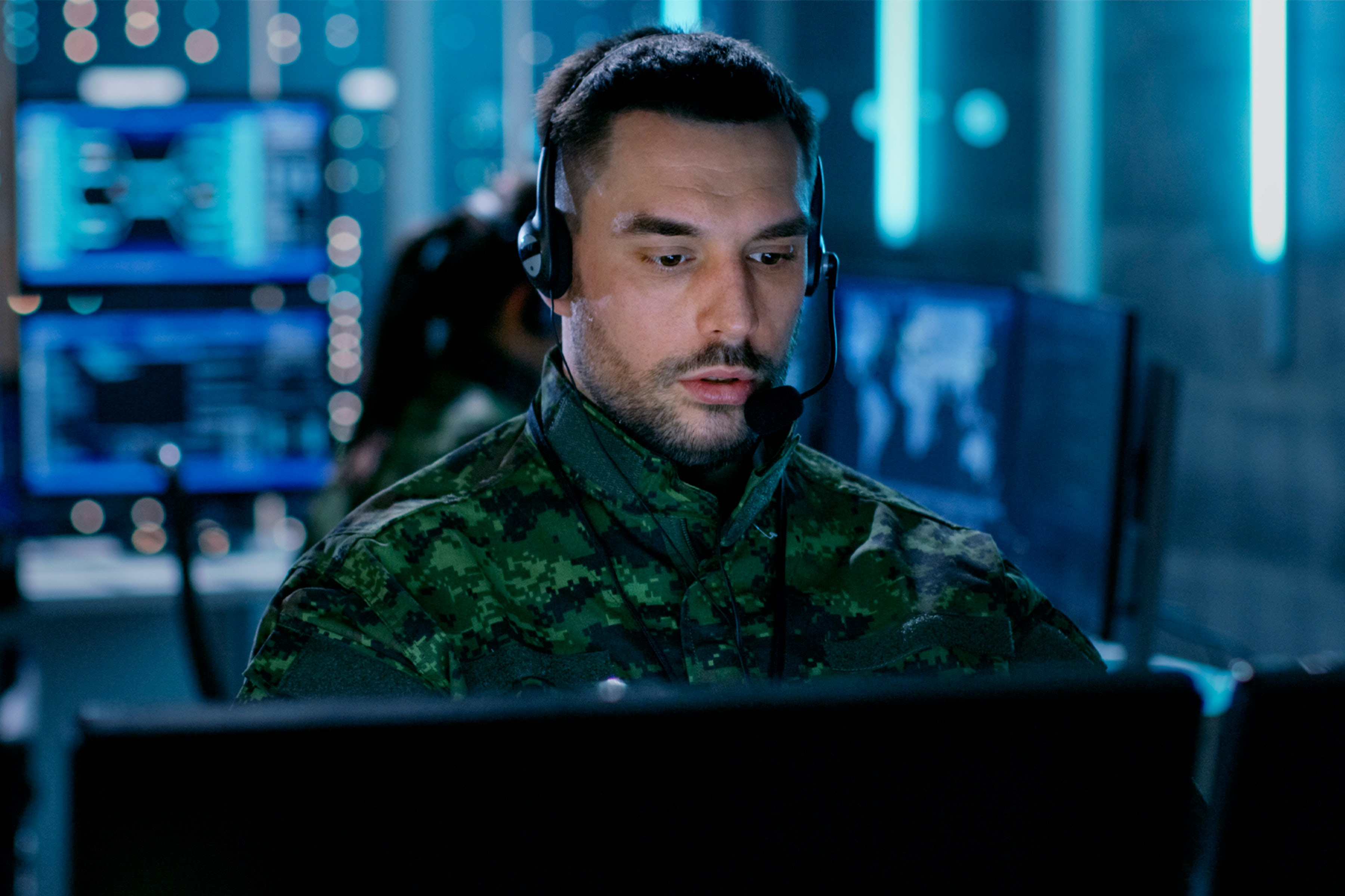 military personnel on computer with a headset