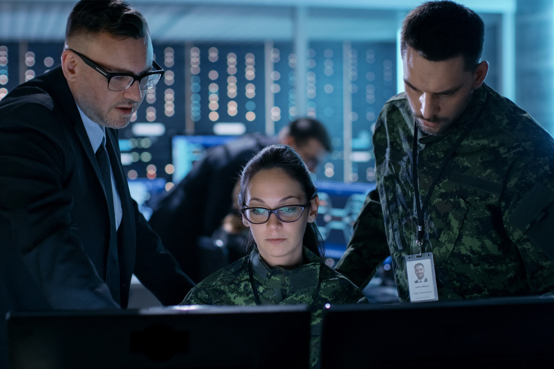 three military personnel look at computer screens together