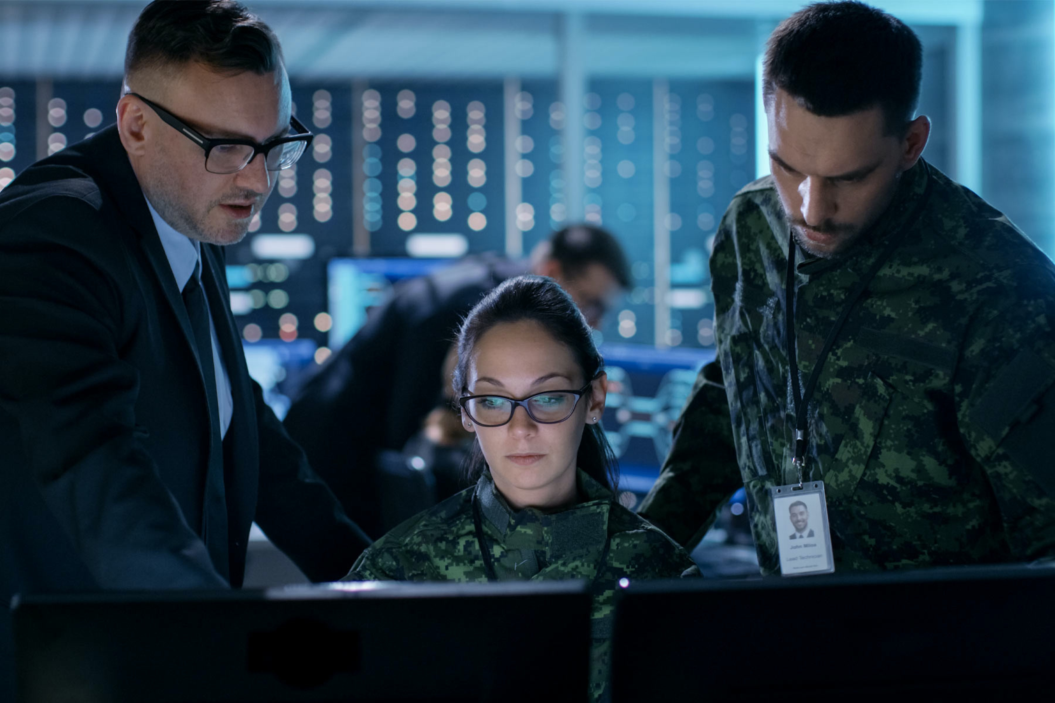 three soldiers looking at computer screens and talking