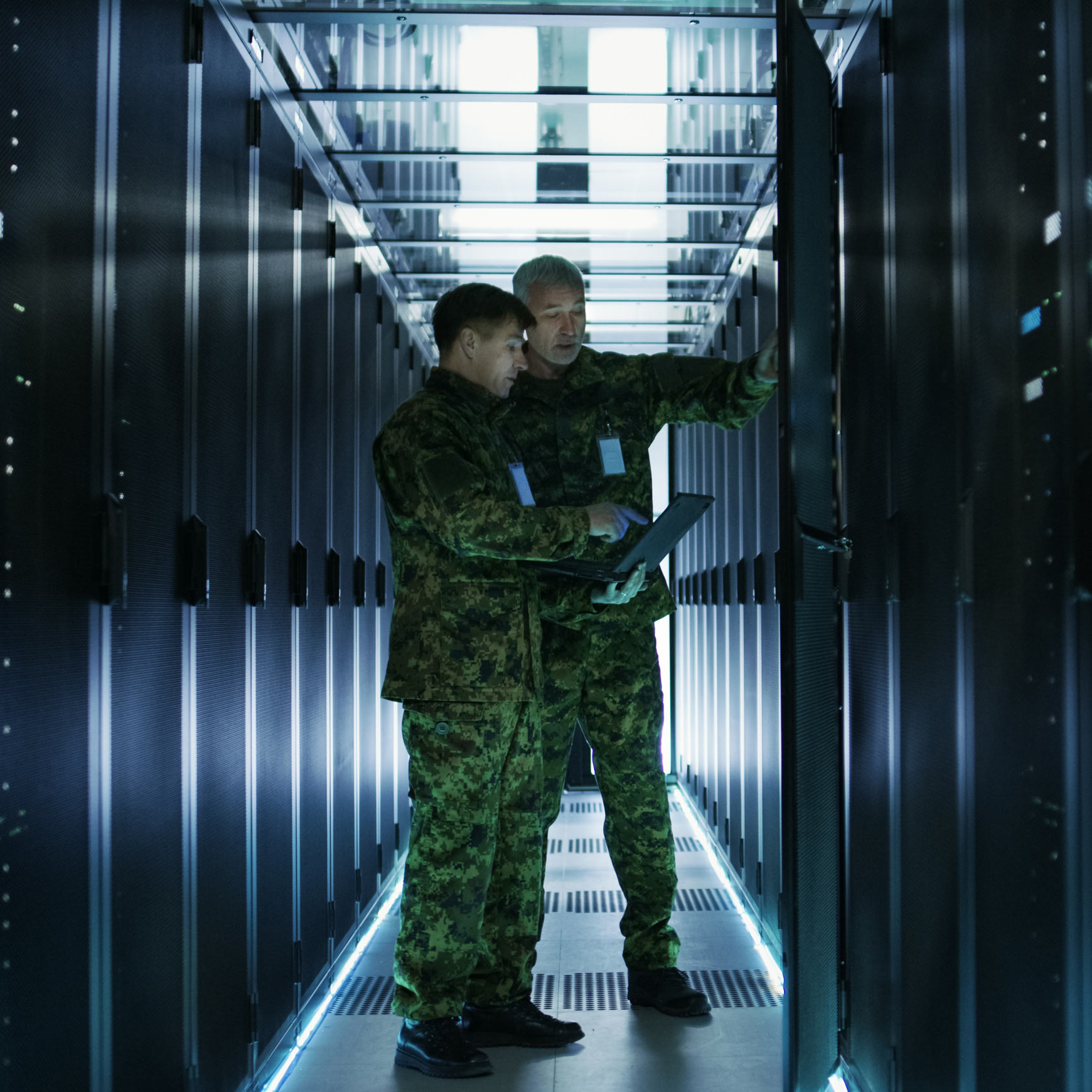 military personnel with tablets next to servers