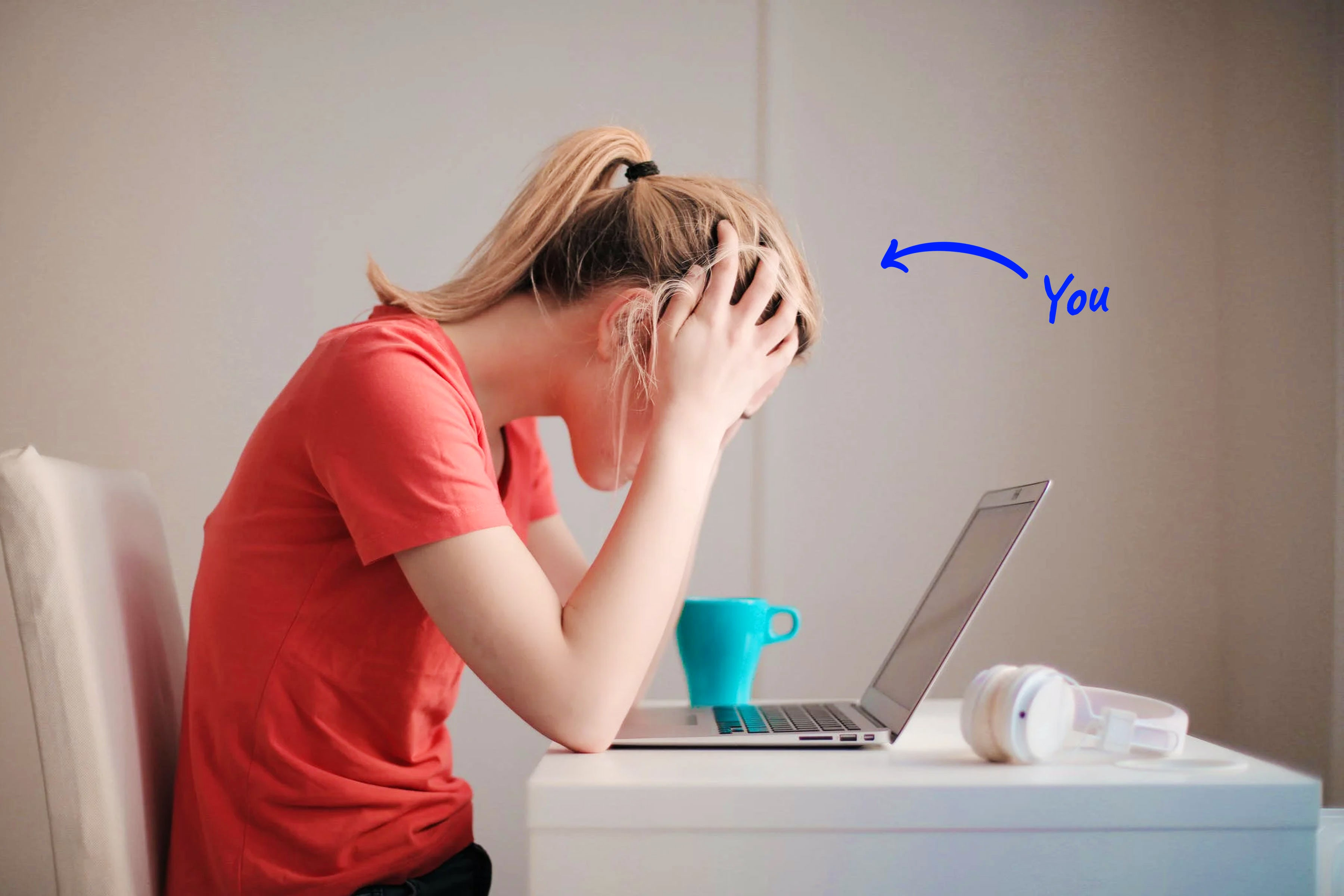frustrated woman looking at laptop with head in hands