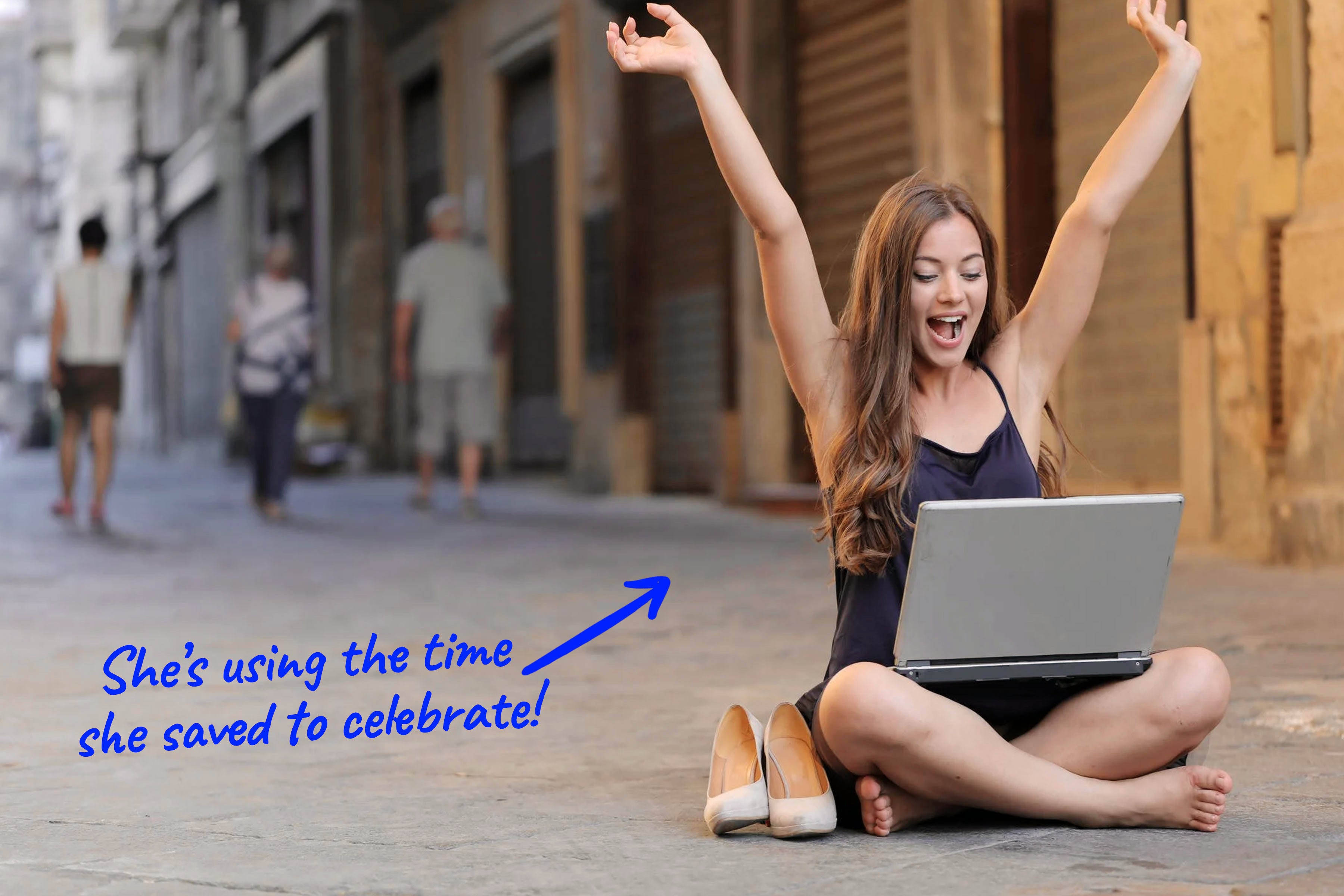 woman sitting on street with laptop cheering