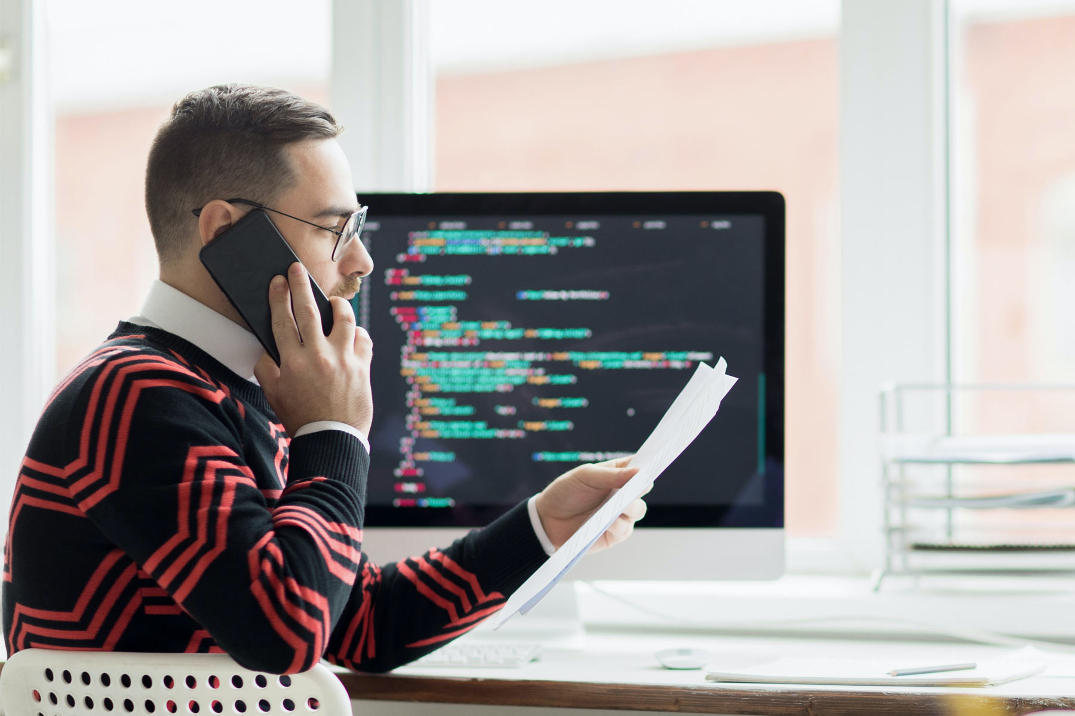 employee on phone looking at document next to computer with code on screen