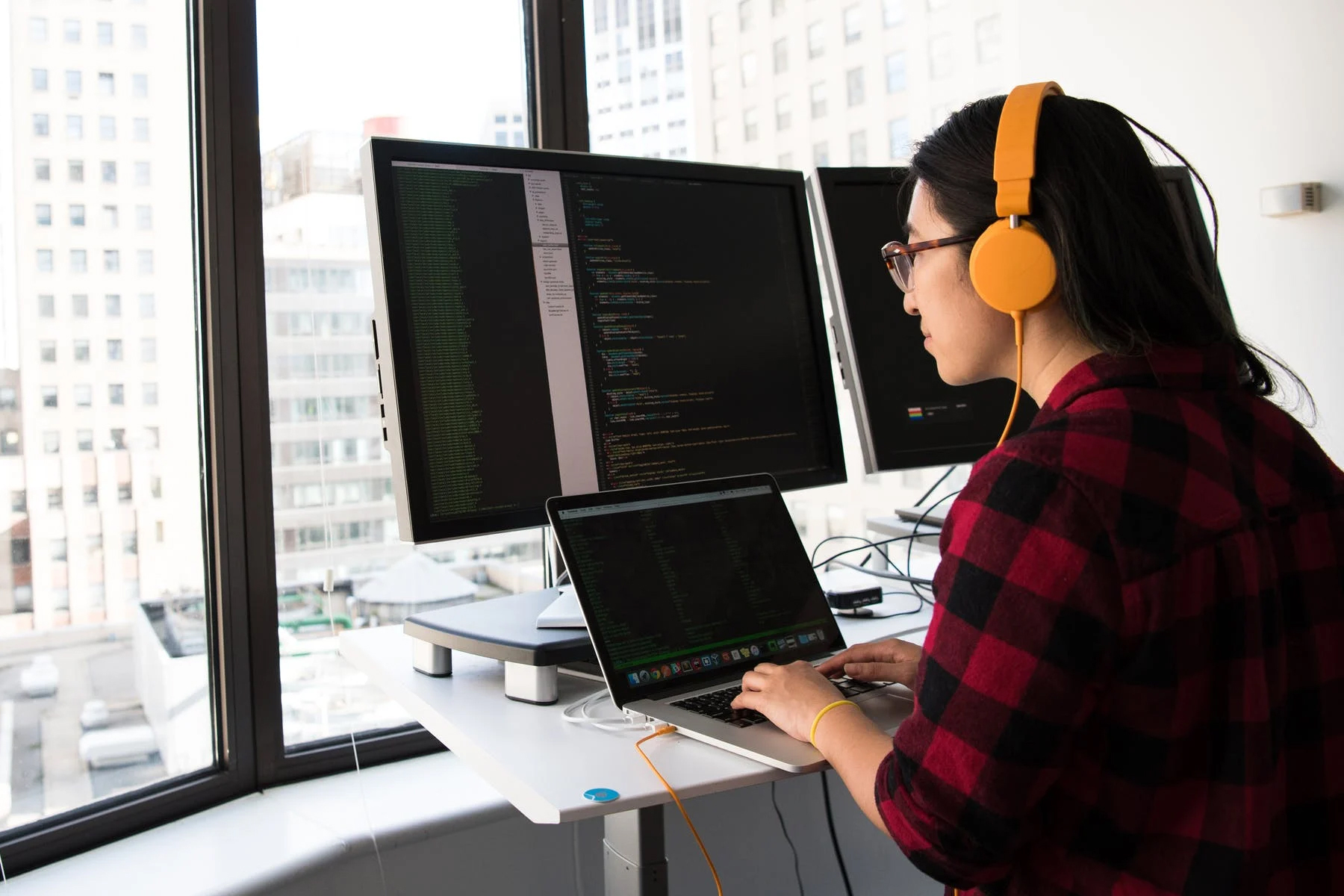 female employee coding on laptop and screens