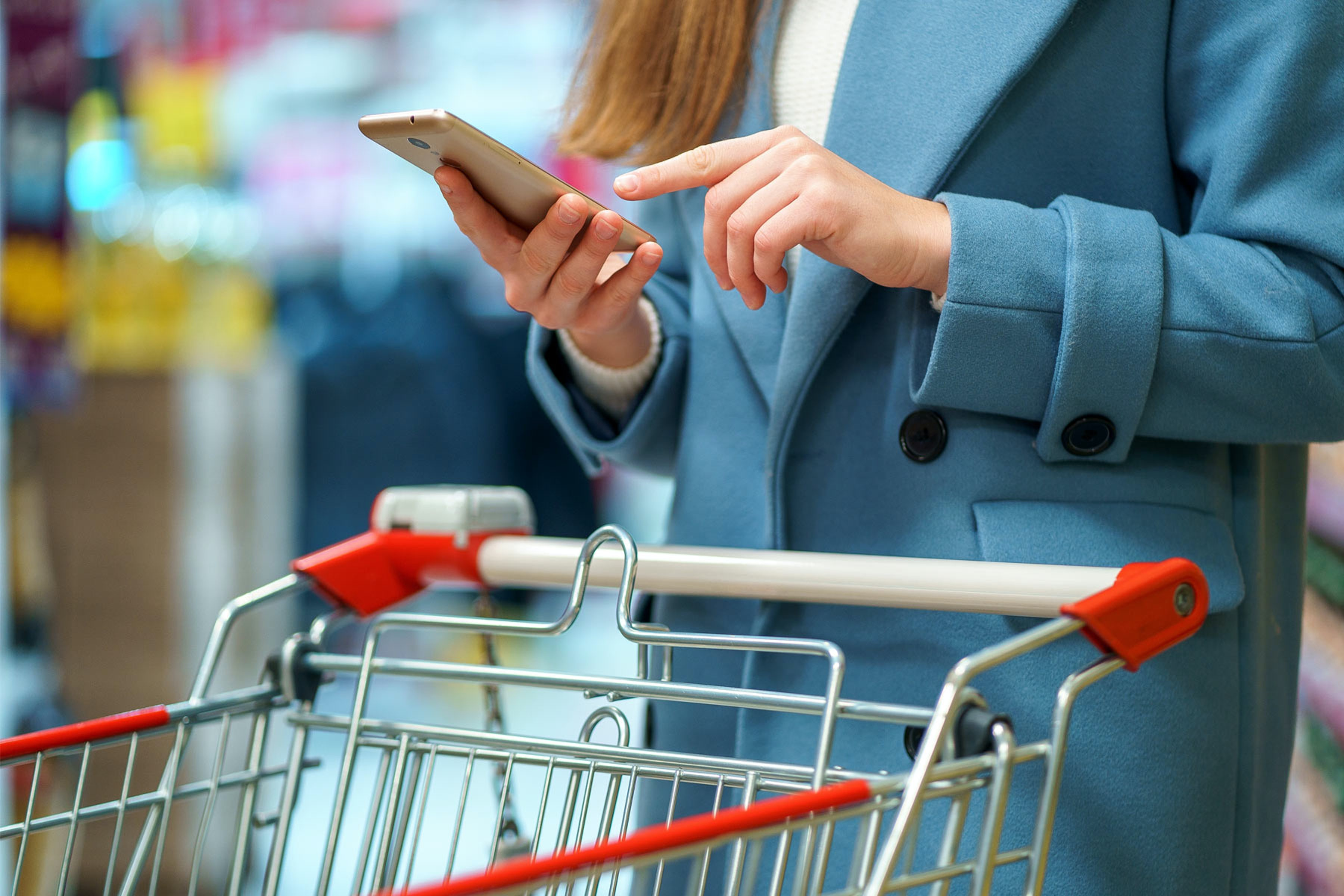 woman using trolley in grocery store on smartphone