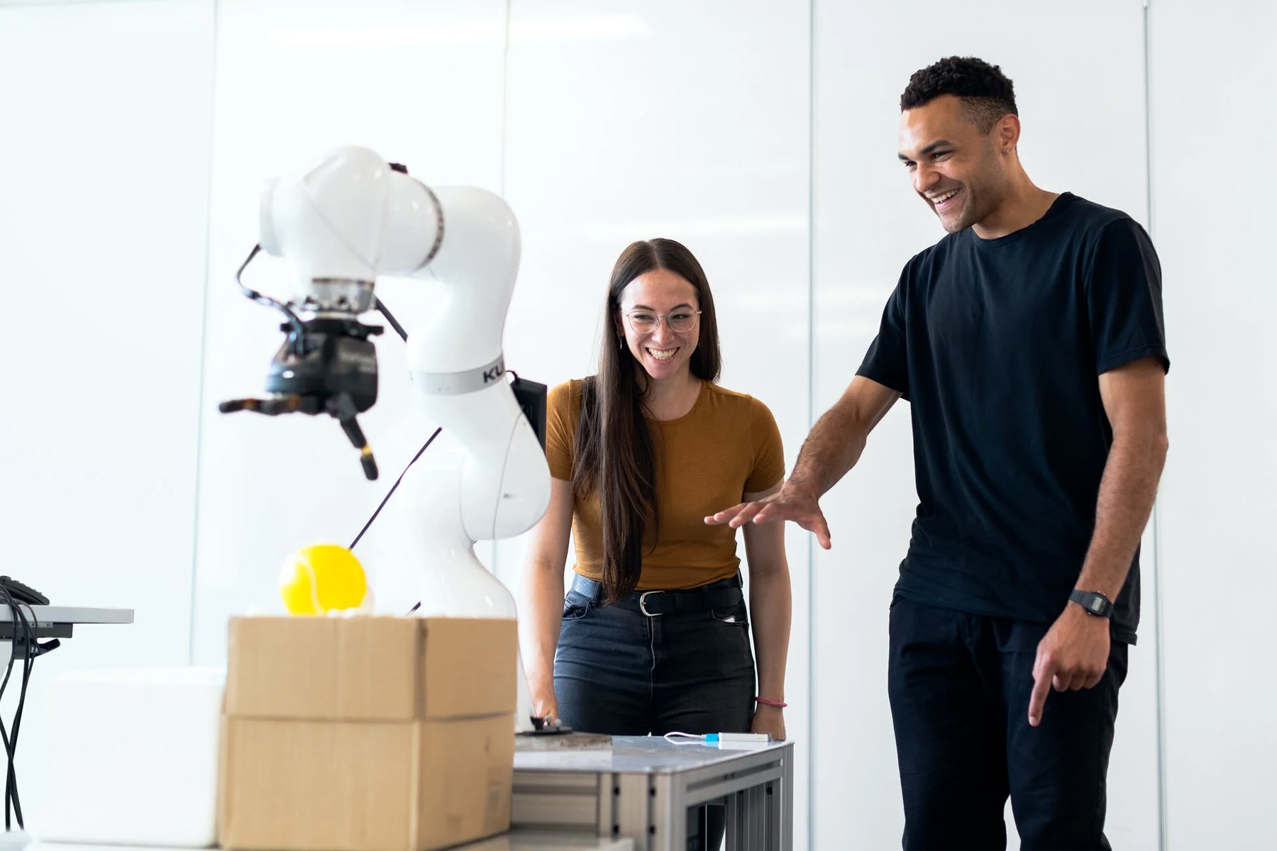 employees looking at a robot as it does a process