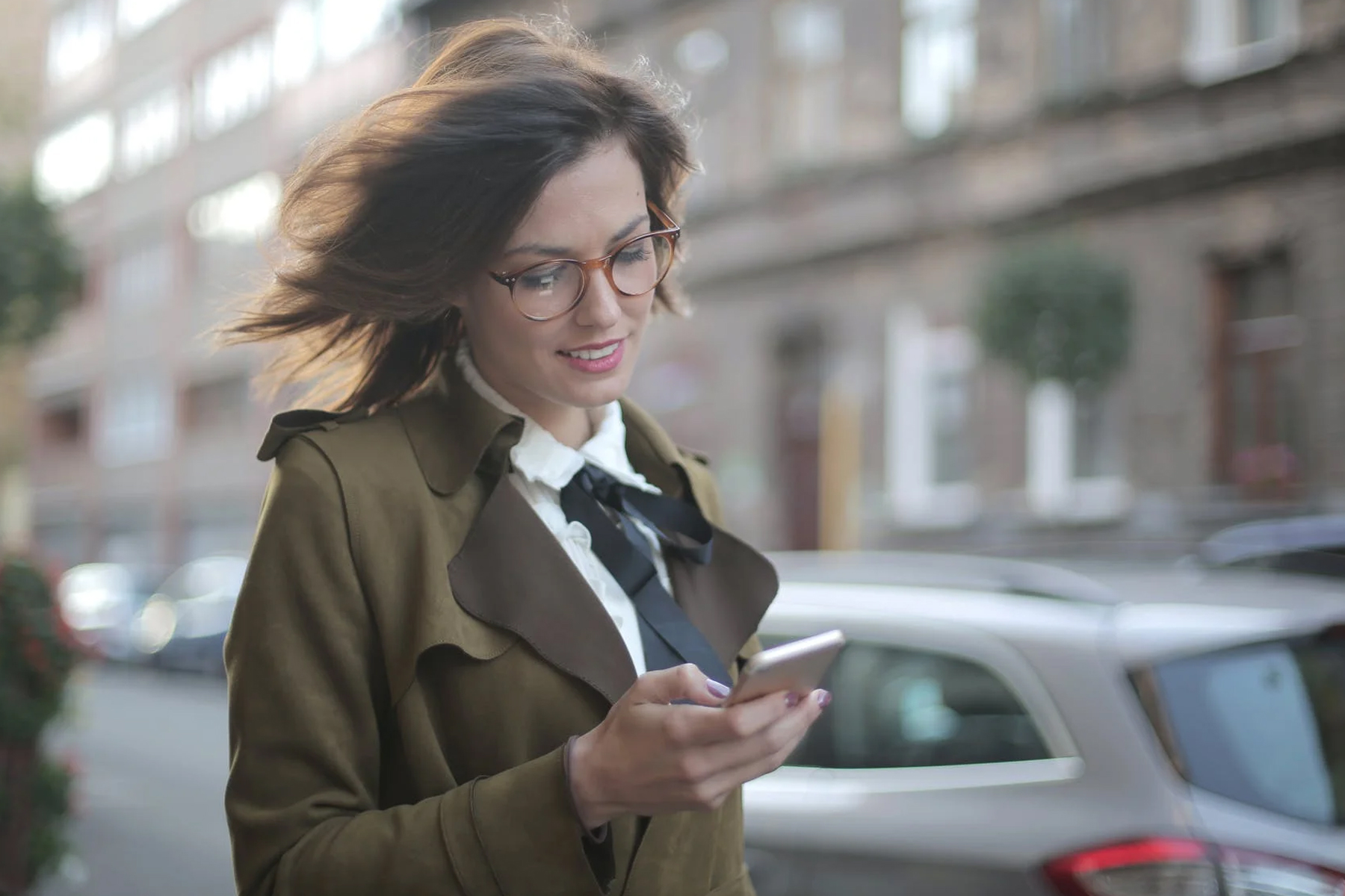 woman looking at smartphone whilst walking down a street