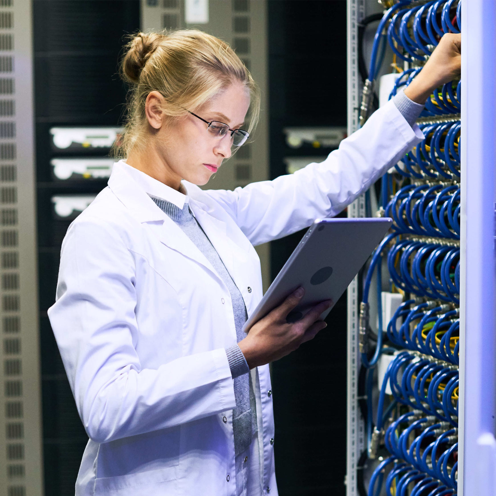woman using tablet next to servers