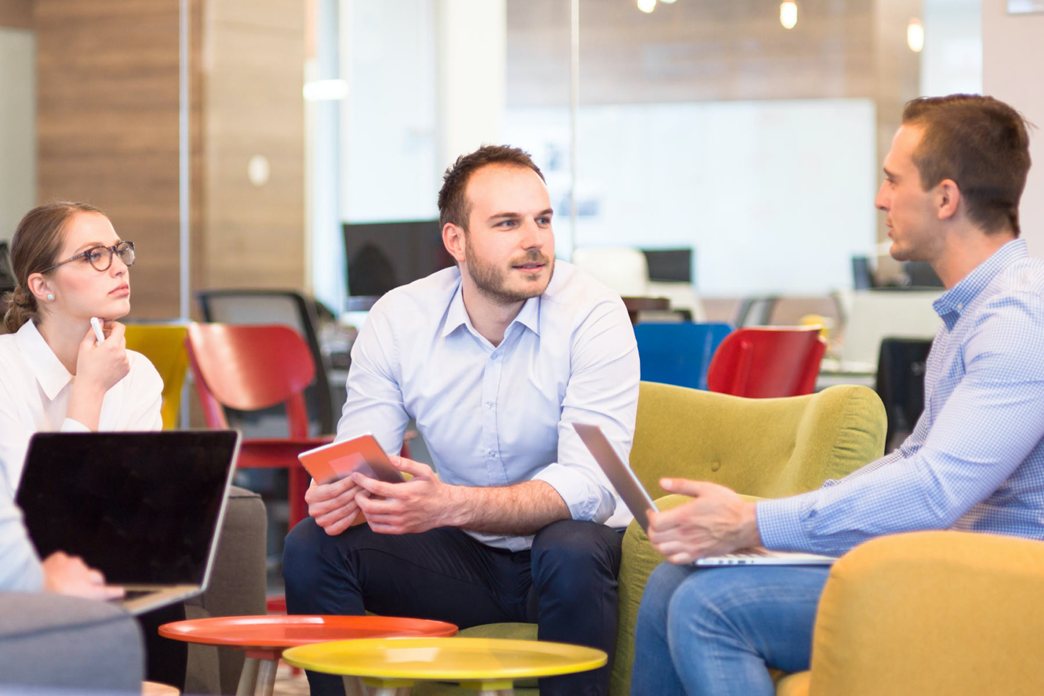 Three employees talking together in open plan office with devices