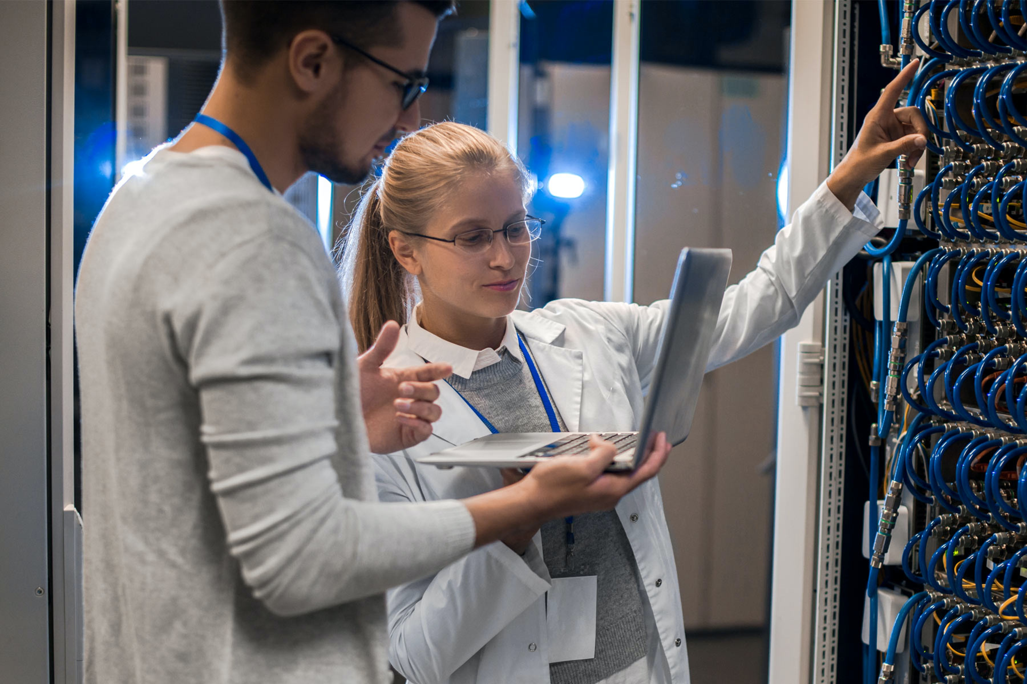 two employees look at a laptop and inspect servers