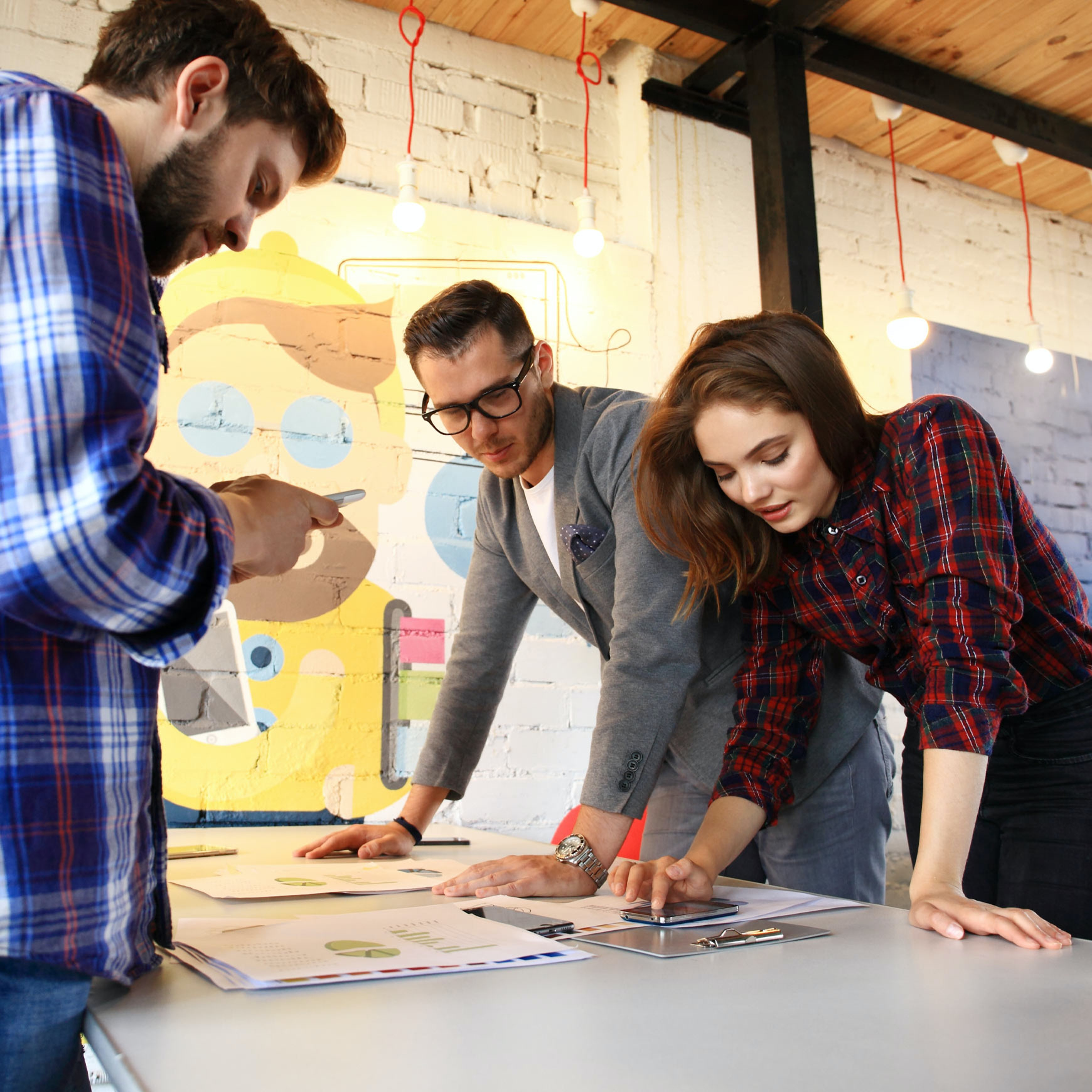 group of employees looking at documents on desk in creative office