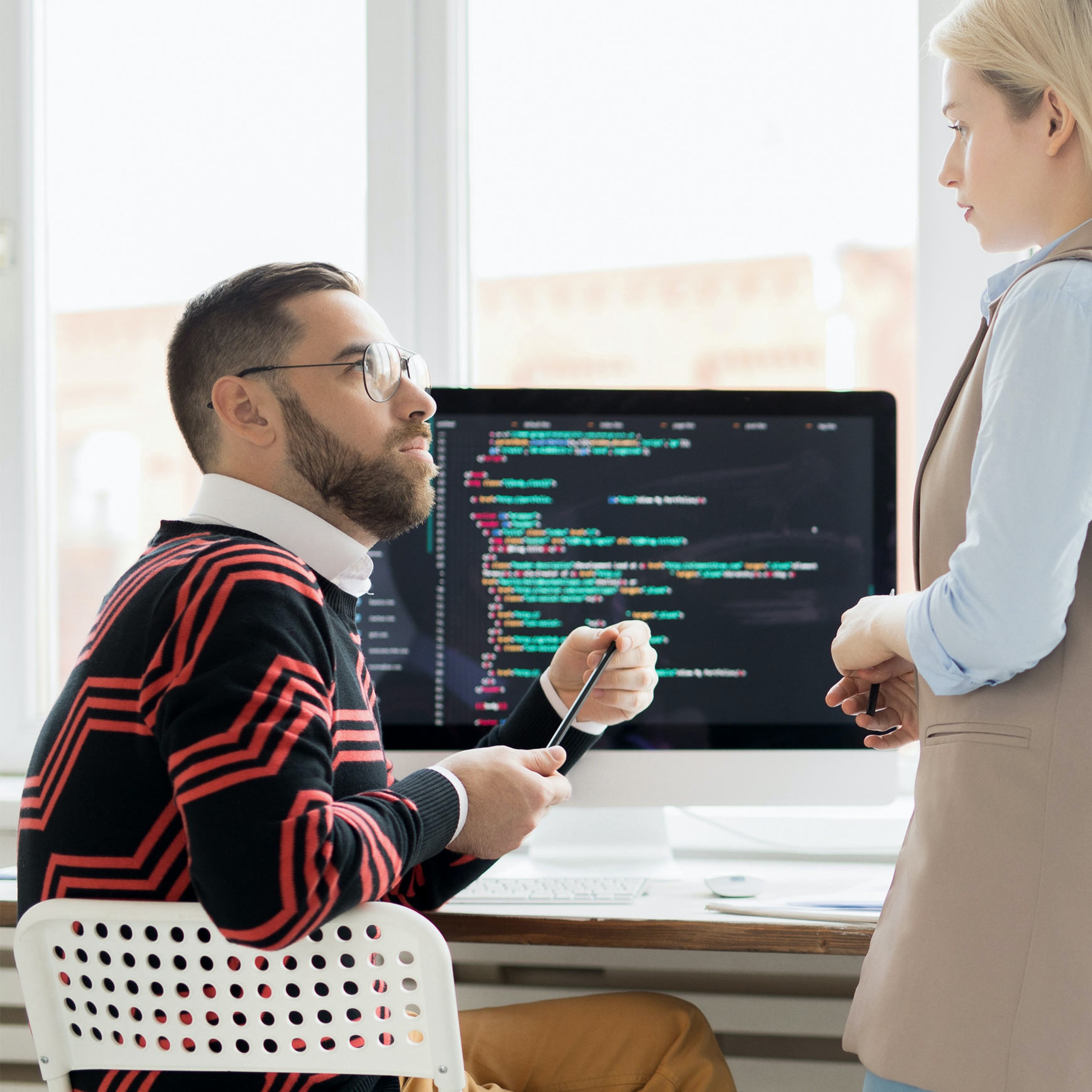 two employees chat in an office with a computer screen of code behind them