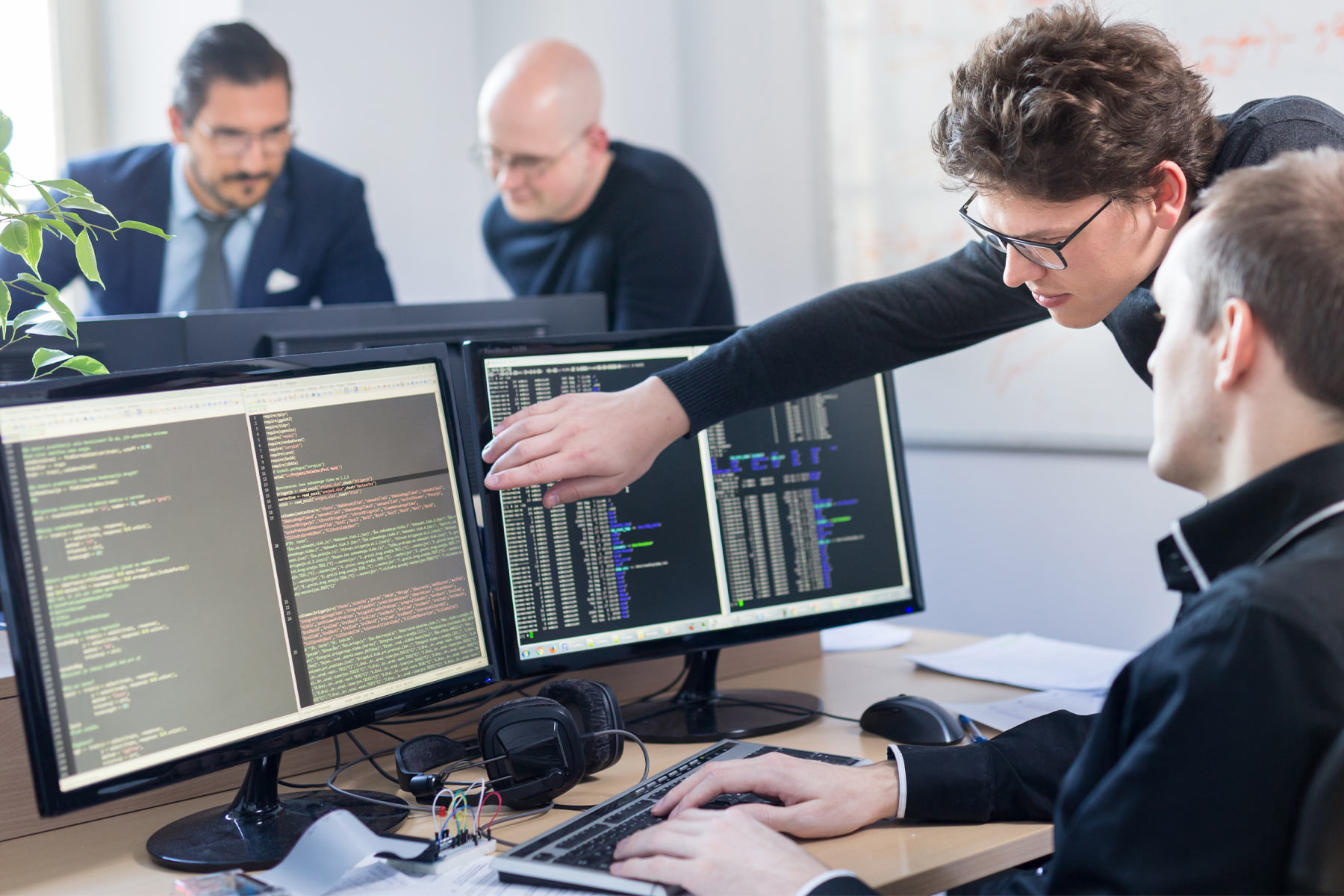 employees looking at coding on computer screens and pointing at it